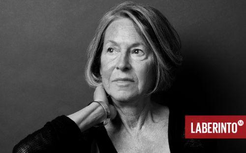 Fotografía en blanco y negro de la poeta Louise Glück en la que aparece del medio pecho hacia arriba, con la mano derecha en el cuello y mirando hacia este mismo lado con una leve sonrisa.