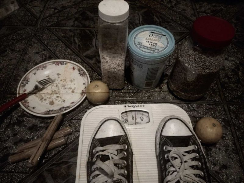 la foro muestra unos tenis sobre una báscula, al rededor hay platos y frascos con semillas, todo en el piso