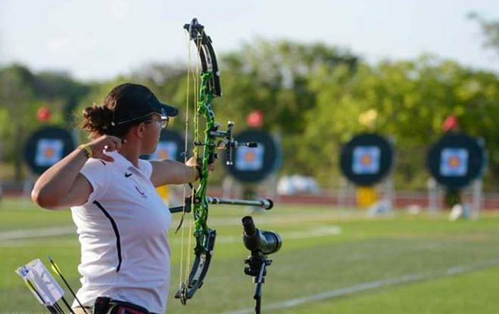 Deporte en la UNAM. Es una fotografía donde Fátima Neri sostiene su arco, ya que acaba de lanzar.
